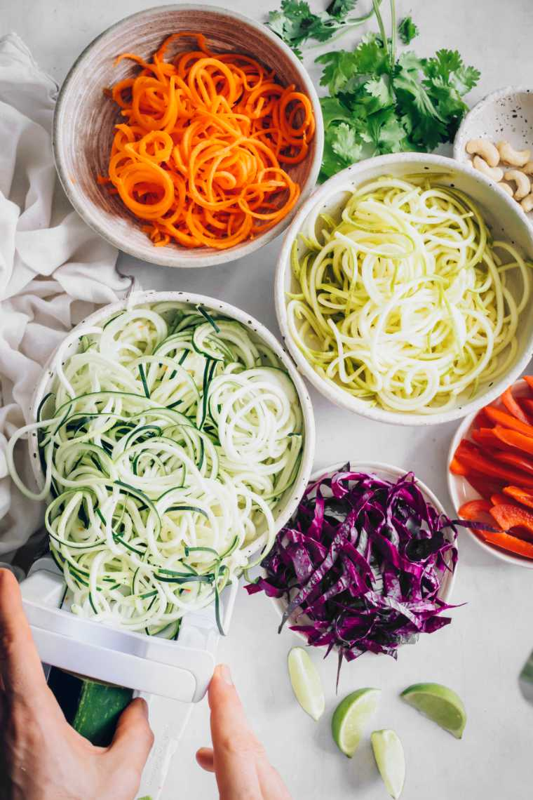 several bowls of spiralized squash, zucchini and carrot as well as sliced red cabbage and bell pepper on a table