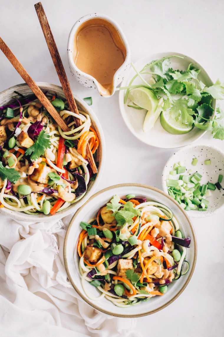 two bowls of colorful spiralized veggies topped with edamame, tofu and a creamy peanut butter sauce