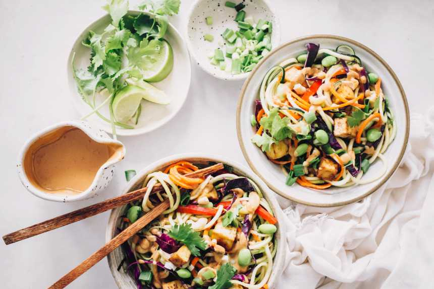 two bowls of colorful raw vegan zoodles with peanut butter sauce and tofu