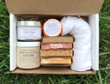 Top view of self care spa box with different components such as soaps, scrubs and shower steamer