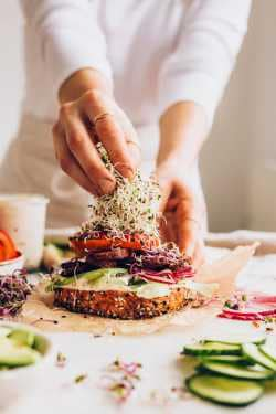 Woman assembling vegan bagels and topping with sprouts