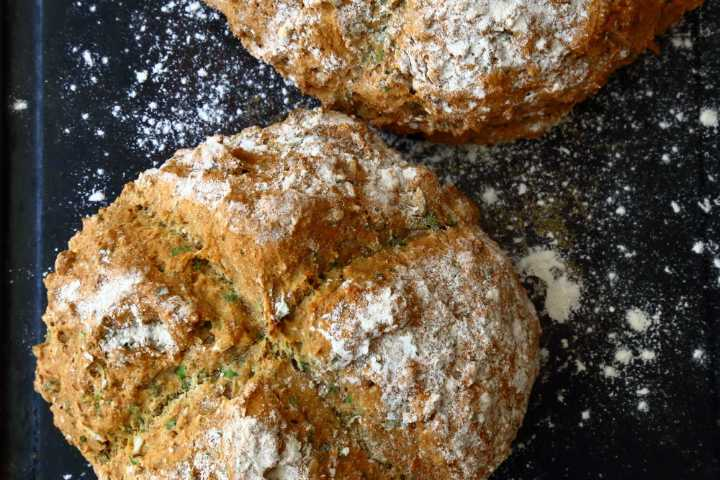 Loaf of soda bread with fresh herbs on dark surface sprinkled with flour