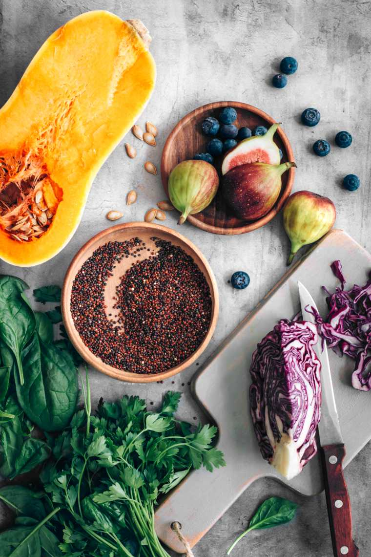 stone surface with a halved butternut squash, fresh figs, blueberries, quinoa, greens and red cabbage