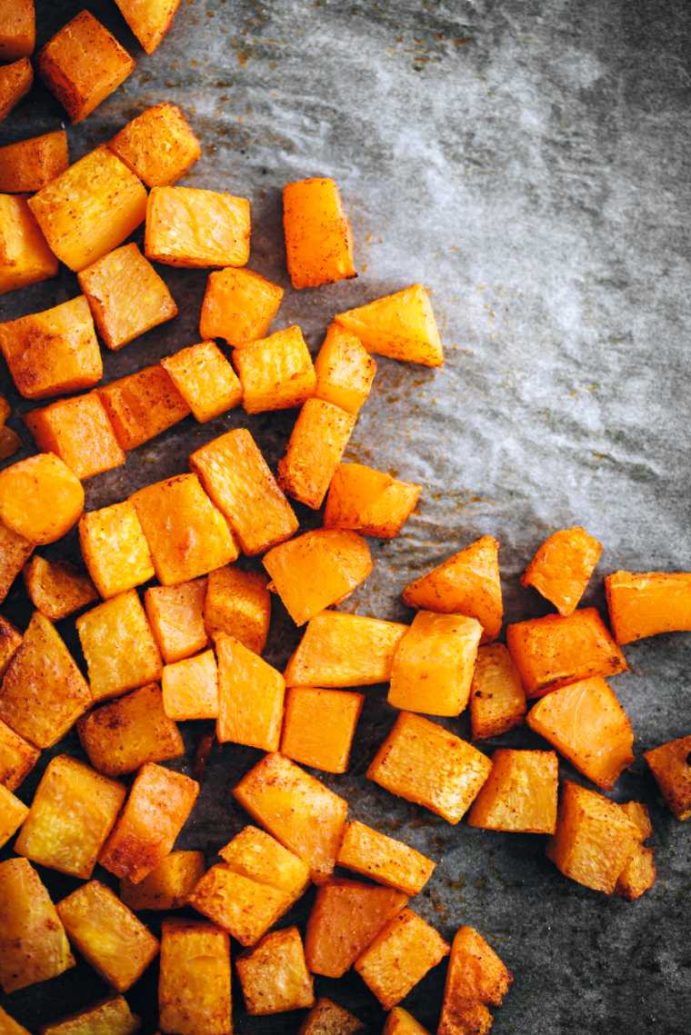 stone table with bright orange cubed and roasted butternut squash