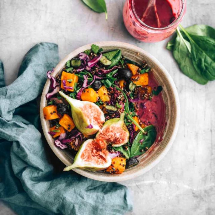 grey bowl with colorful vegan spinach fig salad and an oil-free blueberry dressing
