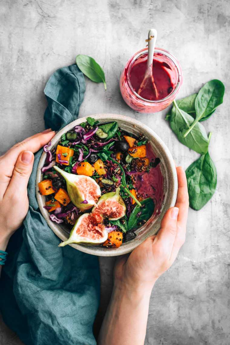 two hands holding a vegan harvest bowl with quinoa, roast pumpkin, spinach, fig and blueberry dressing