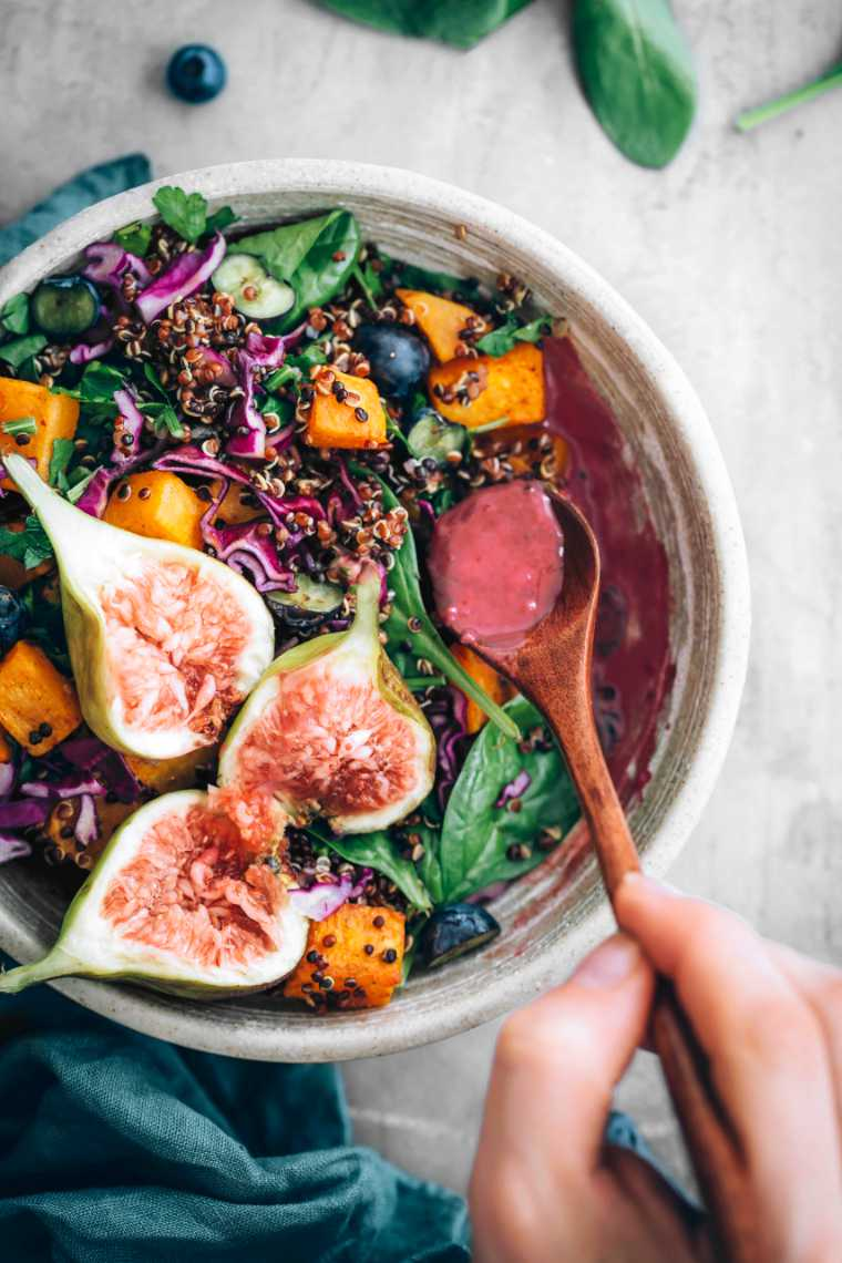 hand drizzling blueberry dressing over vegan harvest bowl with fresh figs and spinach