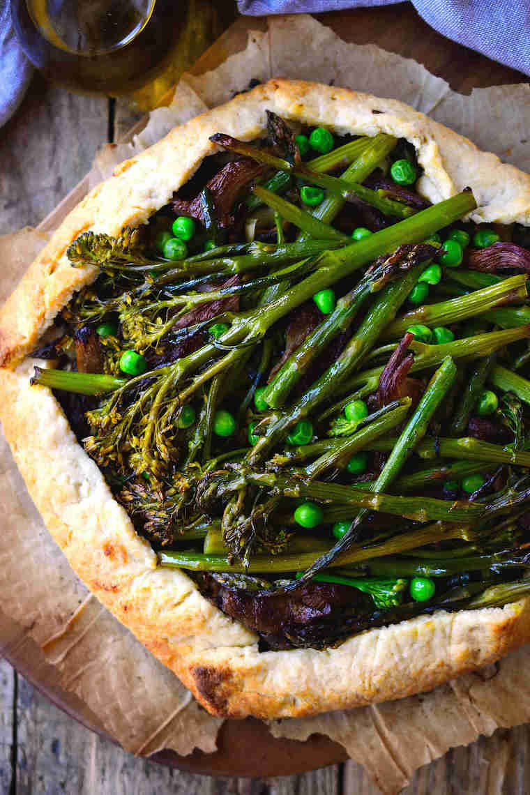 close up of a vegan galette loaded with spring vegetables such as broccoli or asparagus on some parchment paper