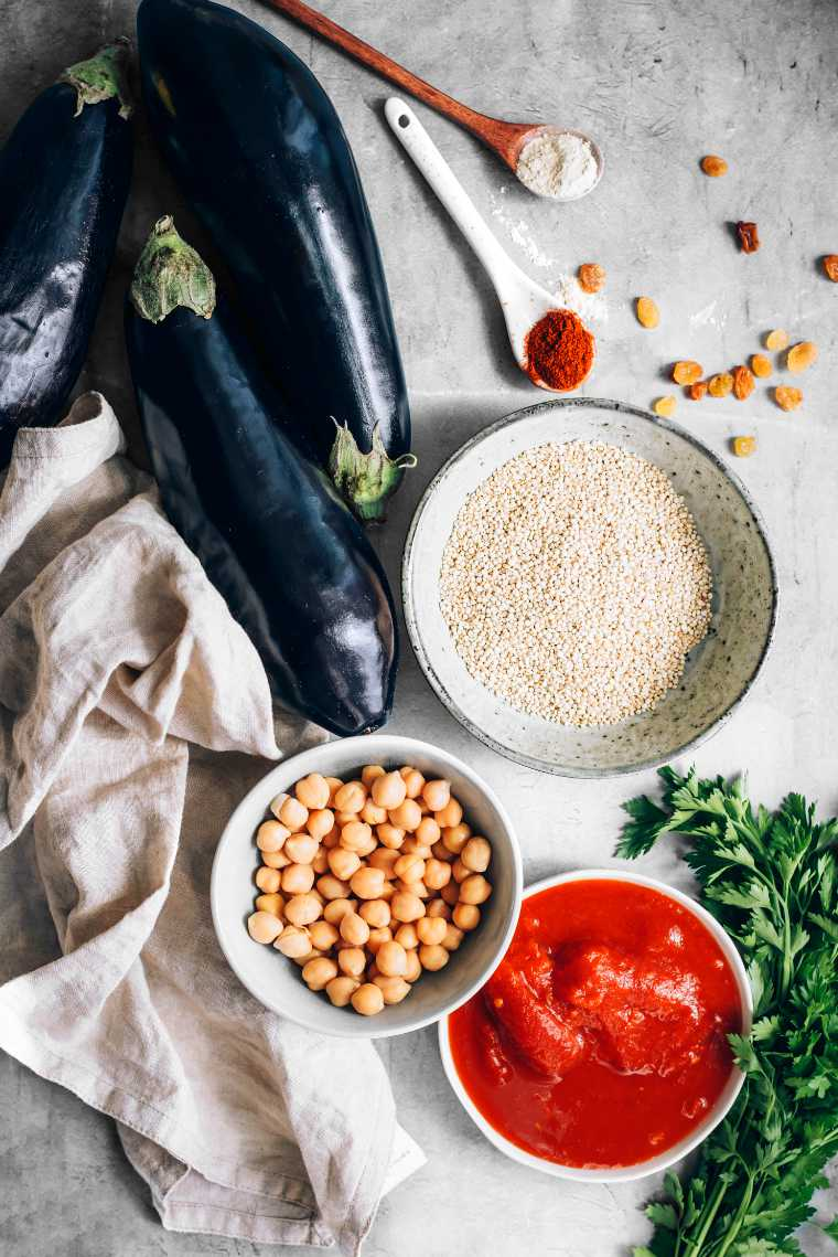 fresh aubergines, uncooked quinoa, chickpeas, tomato sauce and parsley on a table