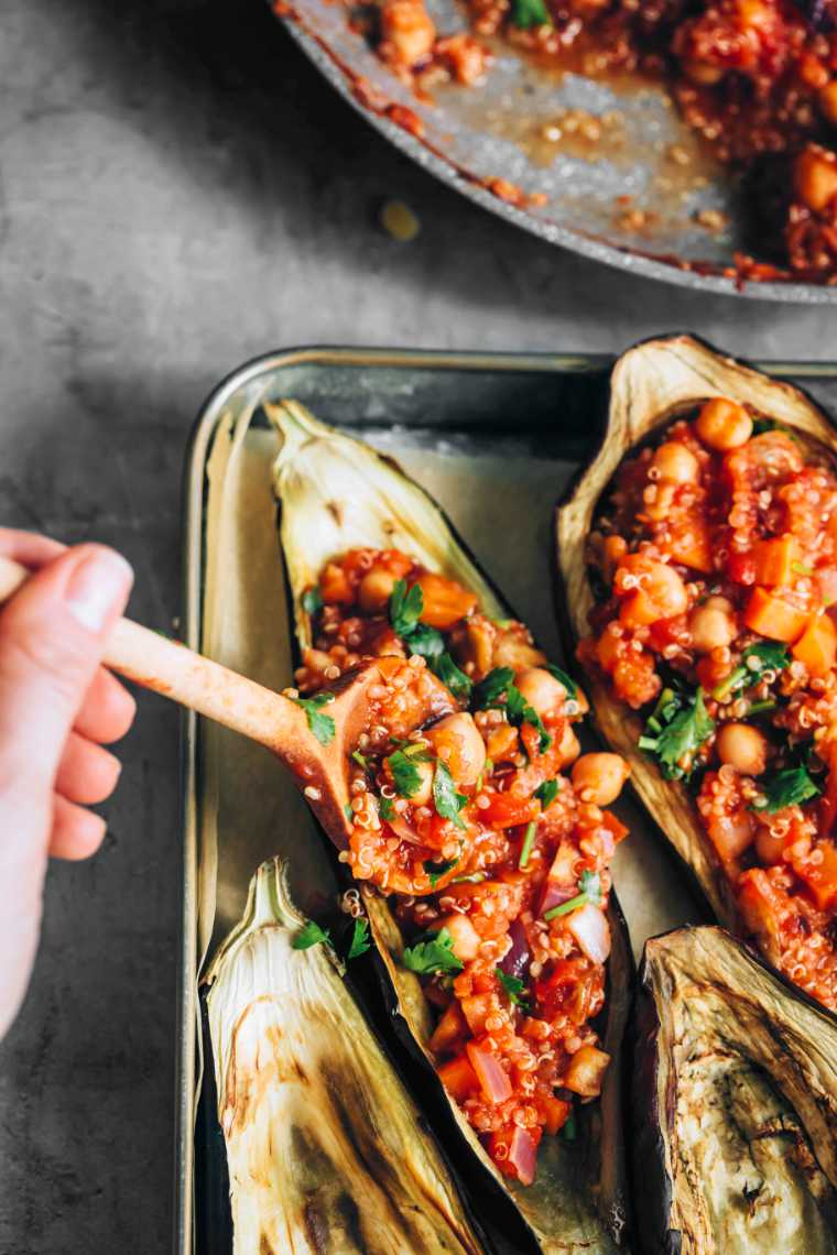 baked aubergines on baking pans being filled with quinoa chickpea mixture