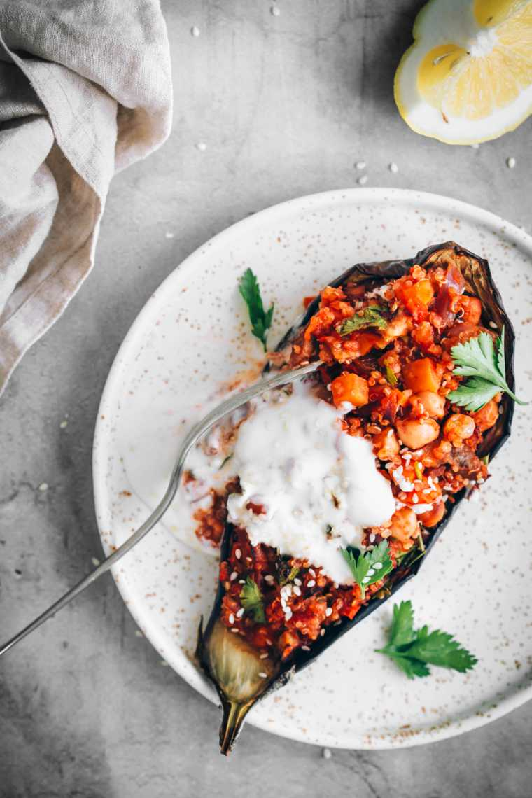 white speckled plate with vegan quinoa stuffed aubergine, soy yogurt and a fork
