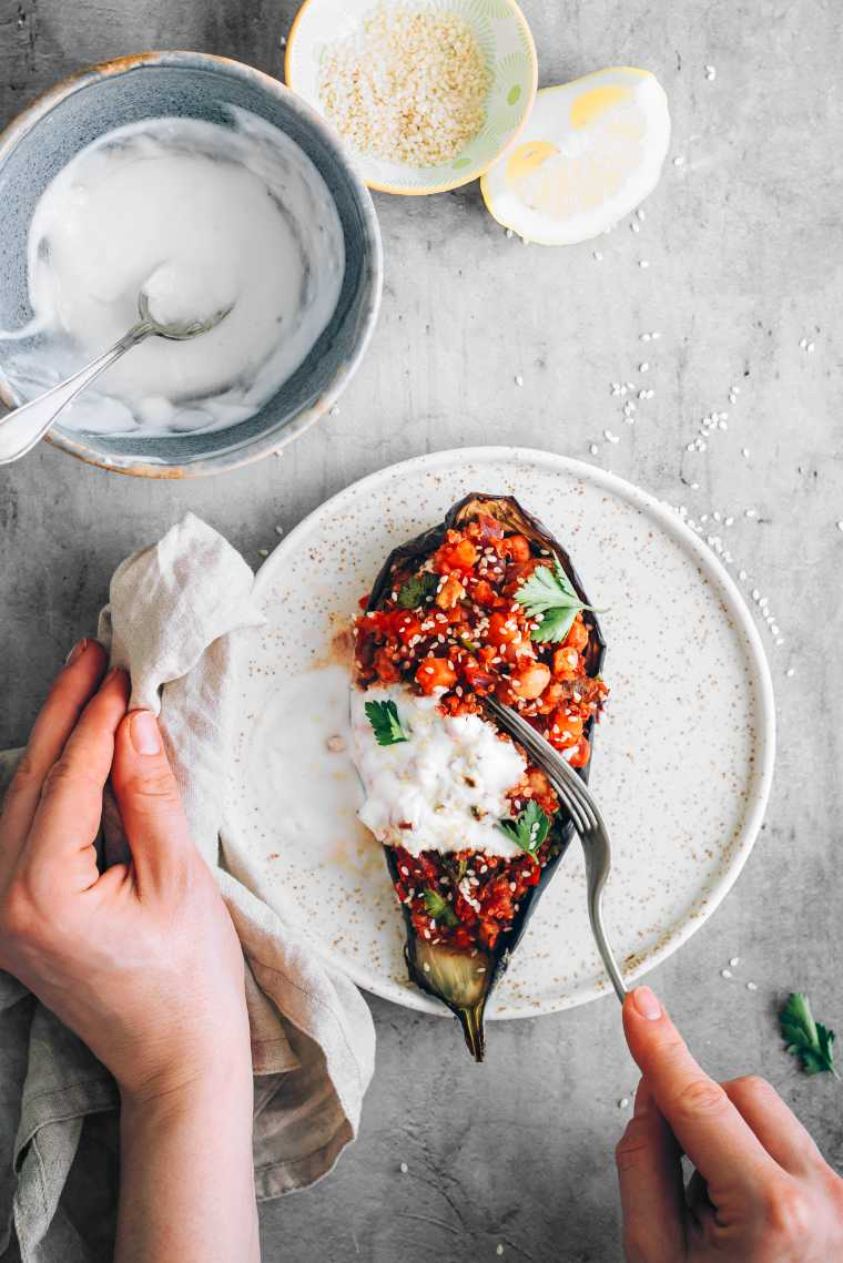 hand holding a white plate and a fork which is cutting into vegan quinoa stuffed aubergine