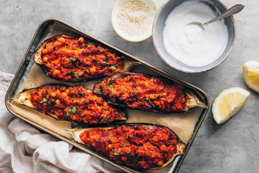 baking dish with four eggplant halves filled with red seasoned quinoa mixture