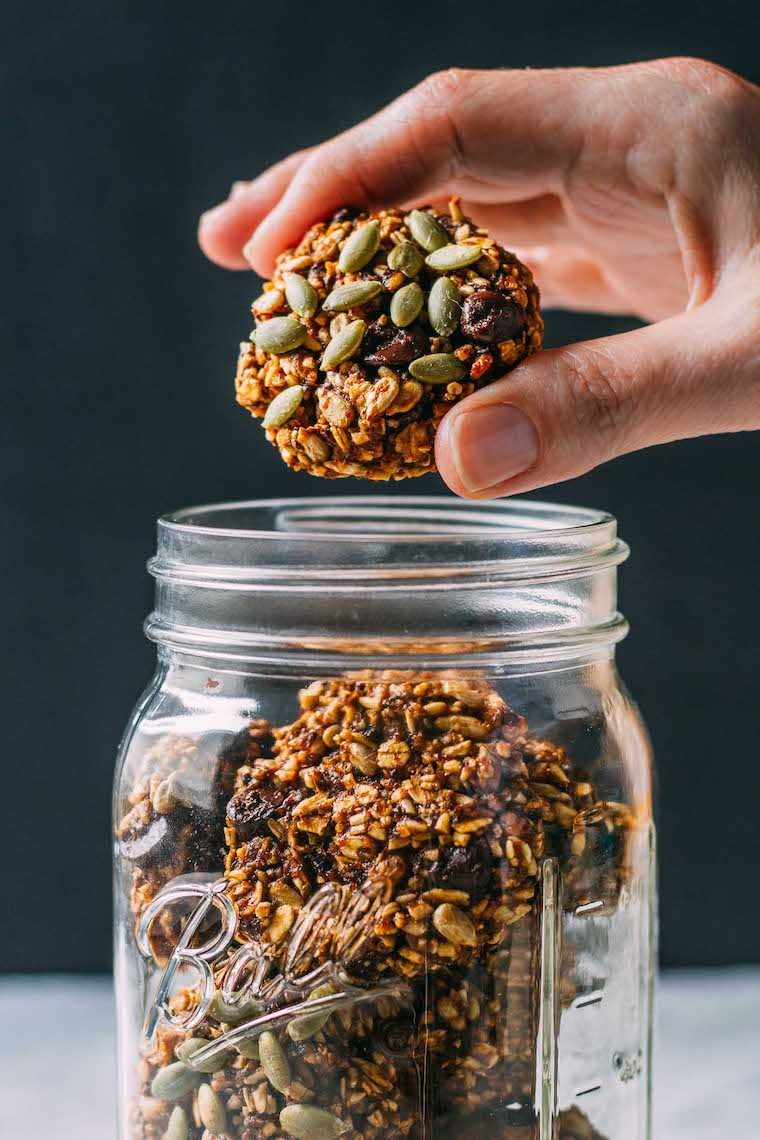 mason jar filled with healthy protein-rich superfood pumpkin cookies, one of which is being taken out by a hand