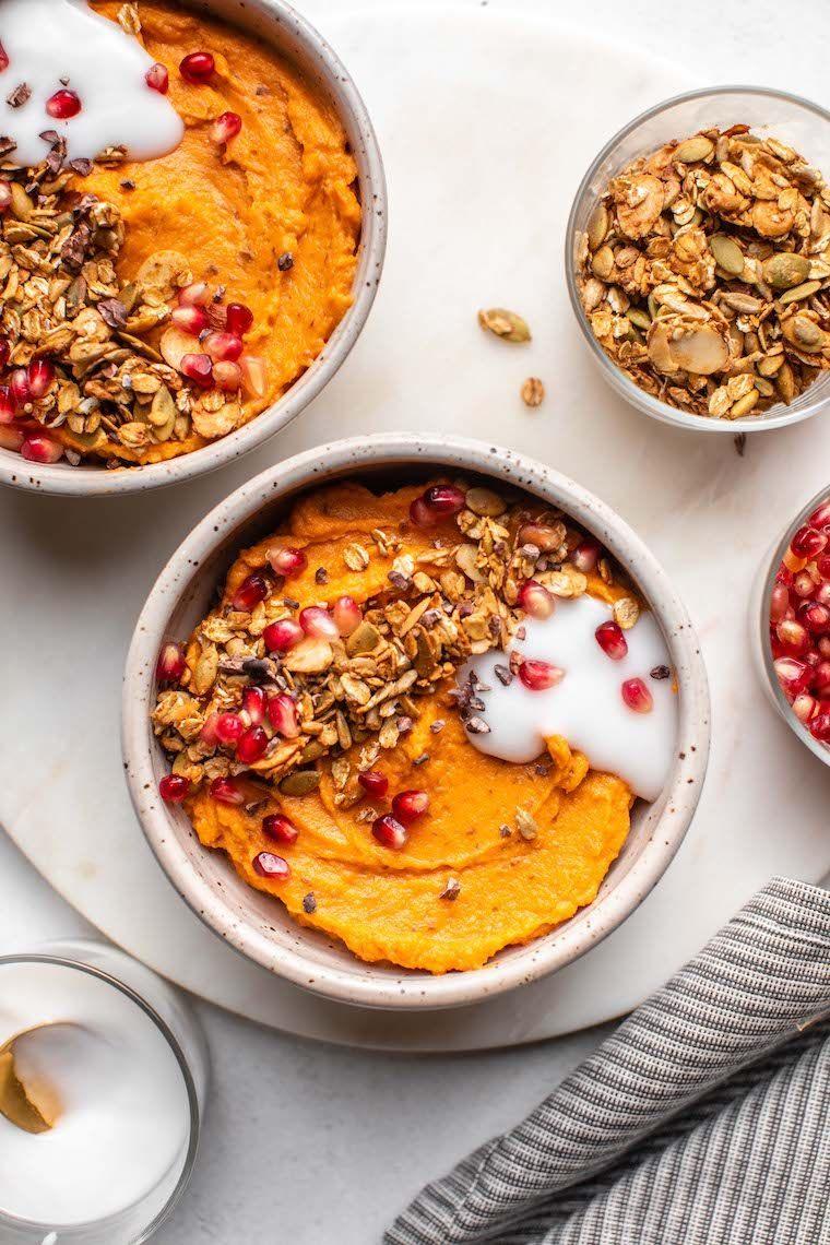 two white bowls with blended orange sweet potato, some granola and vegan yoghurt