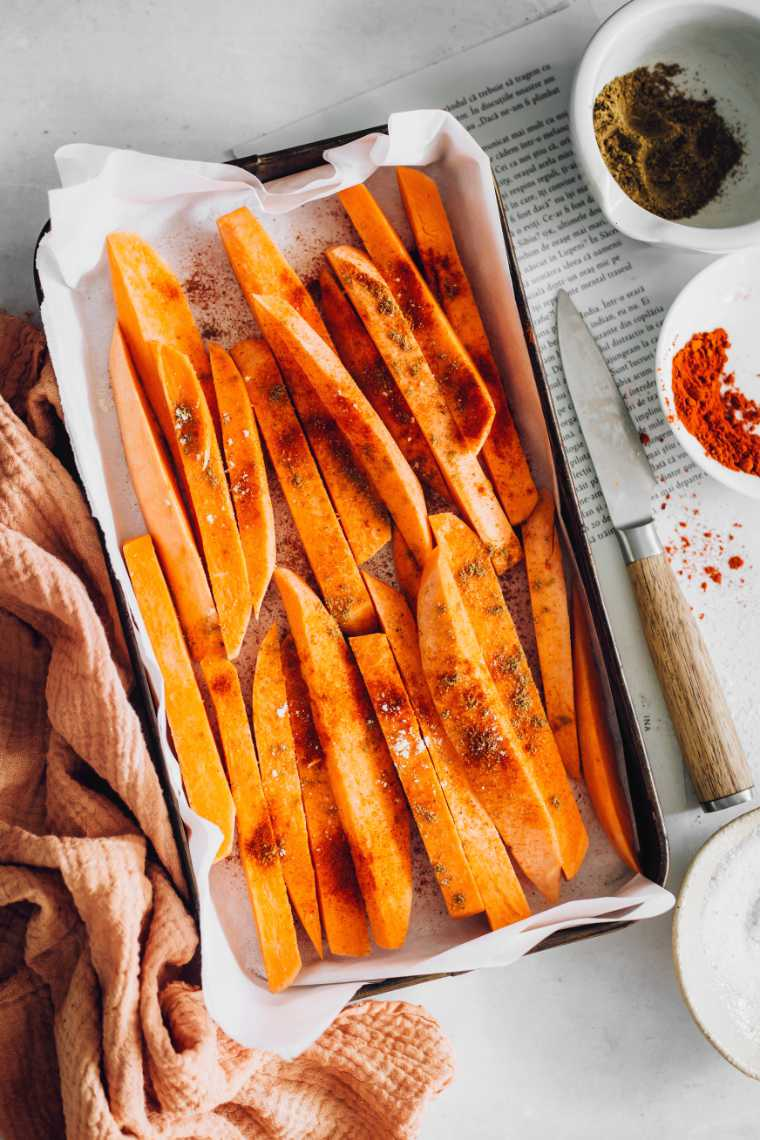 white table with a baking dish lined with parchment paper in which are lots of sliced and spiced orange sweet potatoes