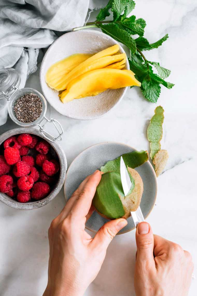 white table with a bowl of sliced mango, one with raspberries and two hands peeling a fresh kiwi