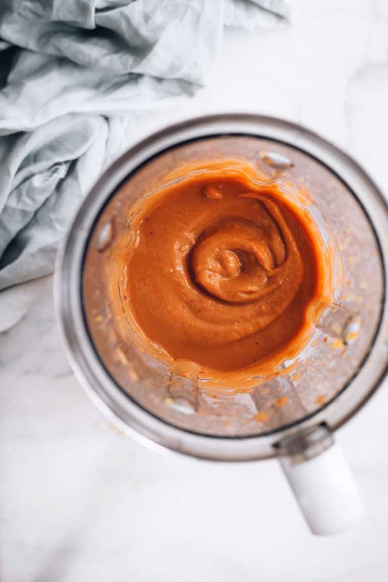 blender jar on a table filled with blended sweet potato