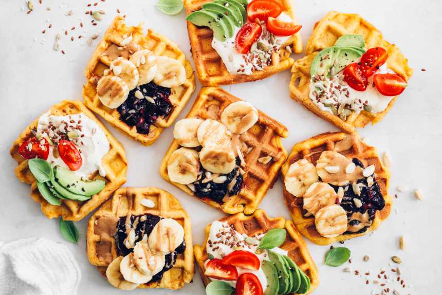 Overhead shot of vegan sweet potato waffles with savory and sweet toppings