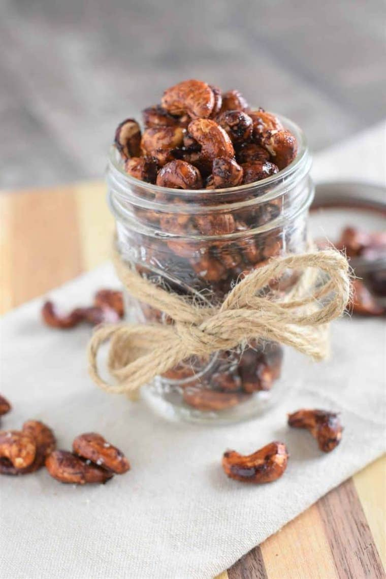 small glass filled with spicy roasted cashews on a cutting board