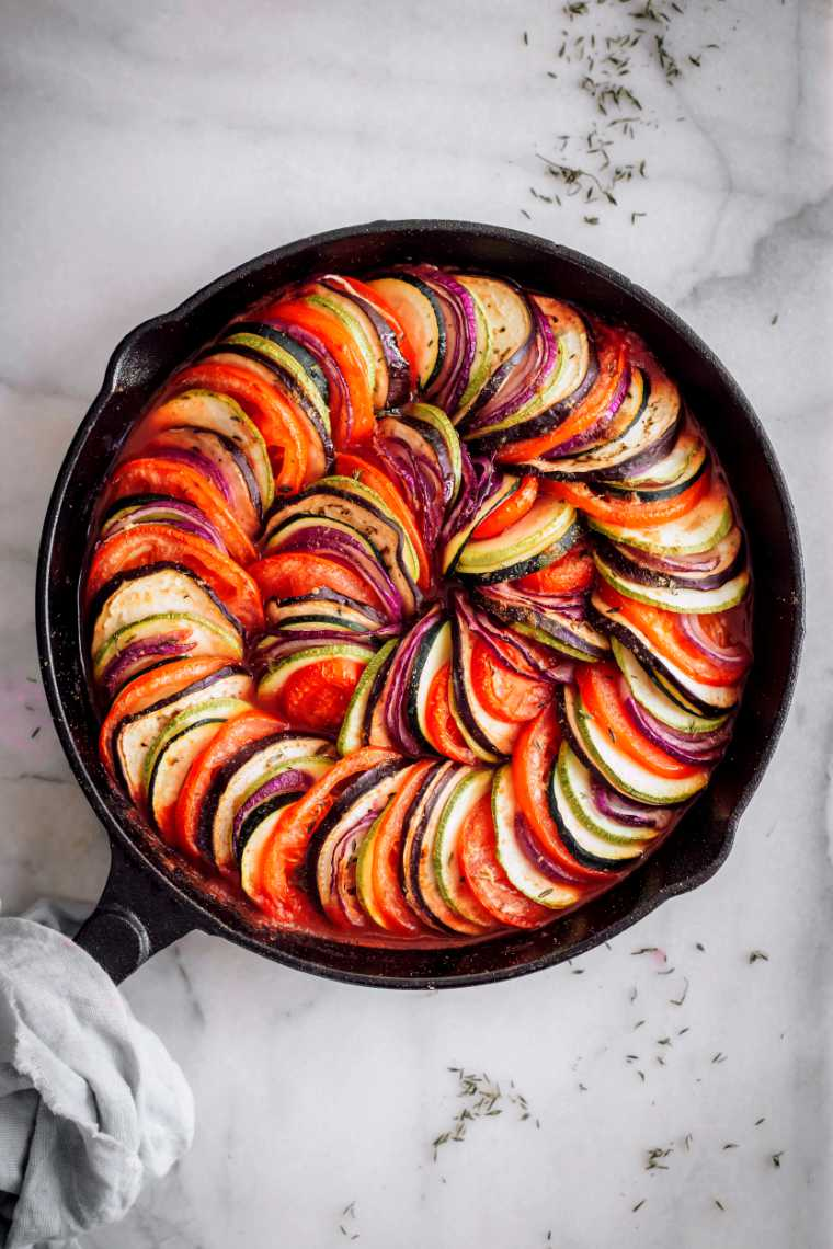 white table with cast iron skillet containing colorful Vegan Tian Ratatouille