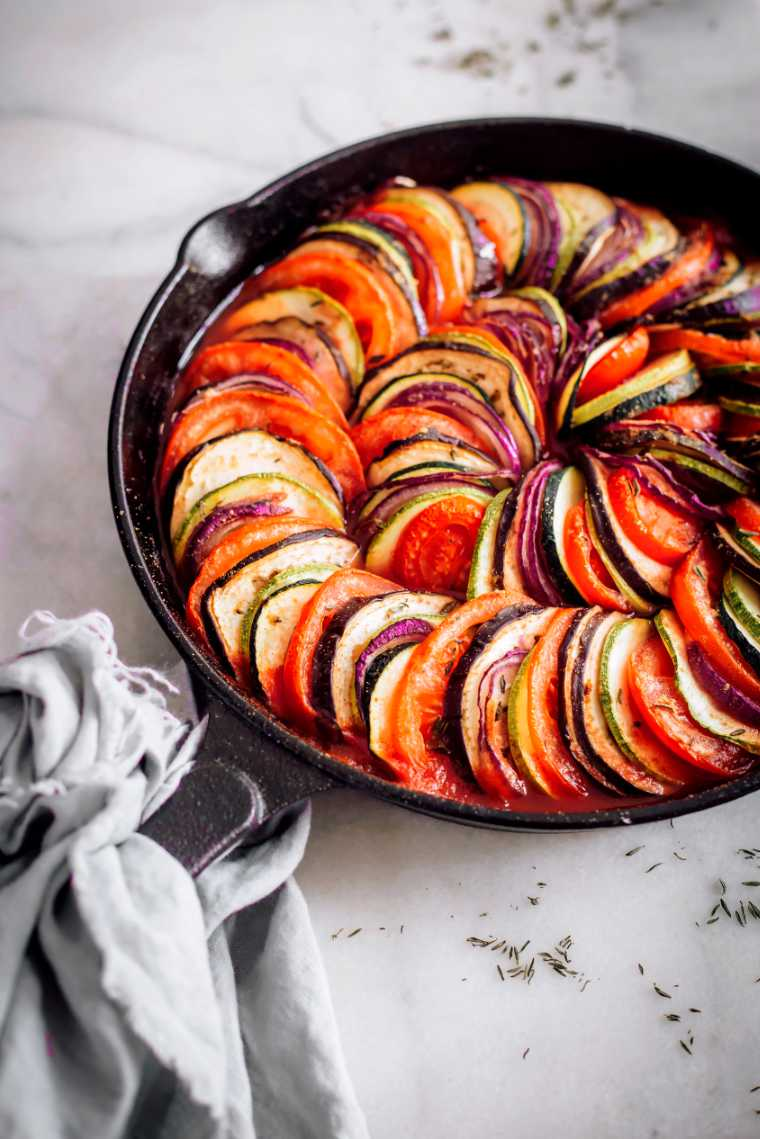 white table with cast iron skillet containing baked layered summer vegetables in tomato sauce