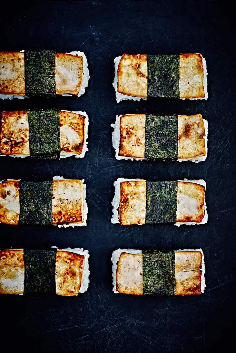 eight little Asian roll ups consisting of white rice, marinated tofu and seaweed on a dark table