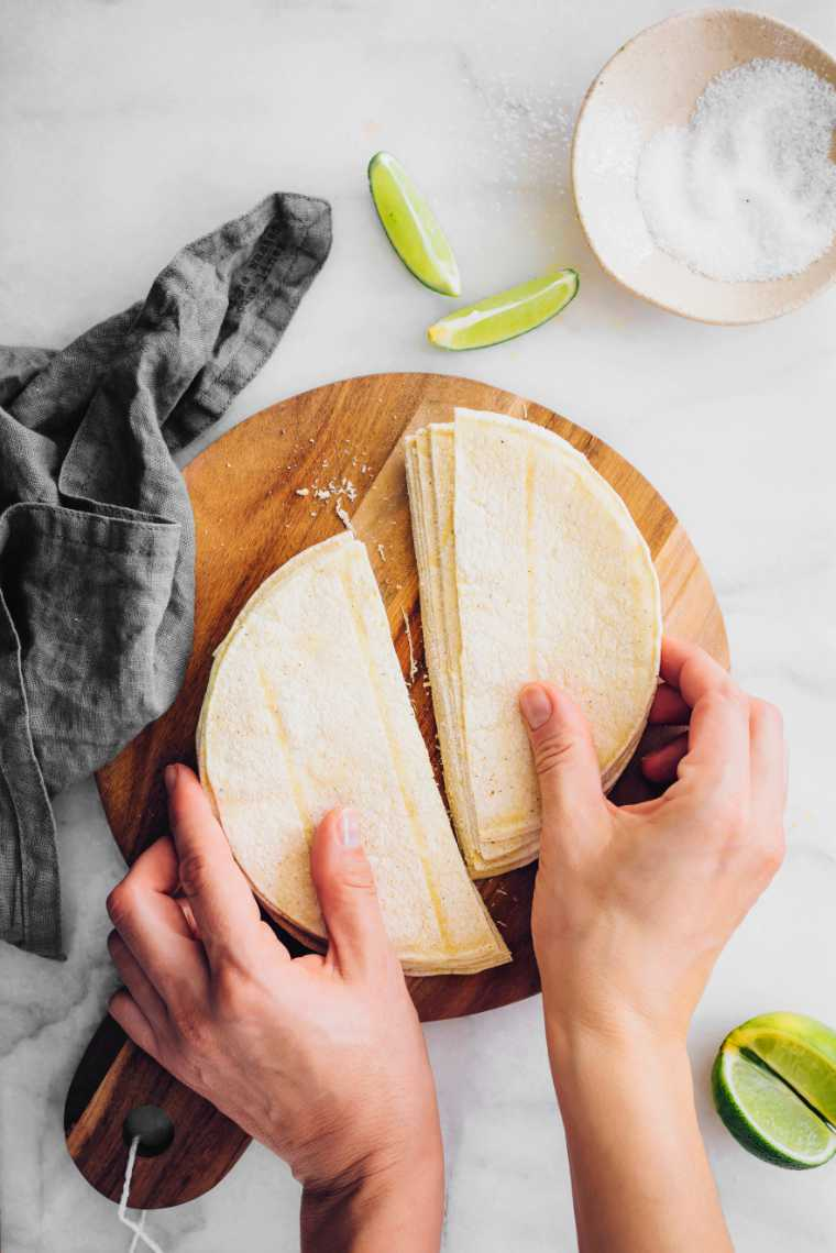 white table with wooden cutting board and halved corn tortillas held by hands