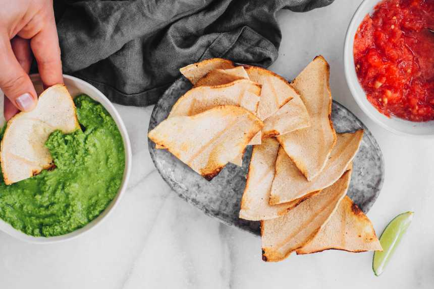 hand holding gluten-free tortilla chip and dipping it into vegan guacamole next to more oil-free chips