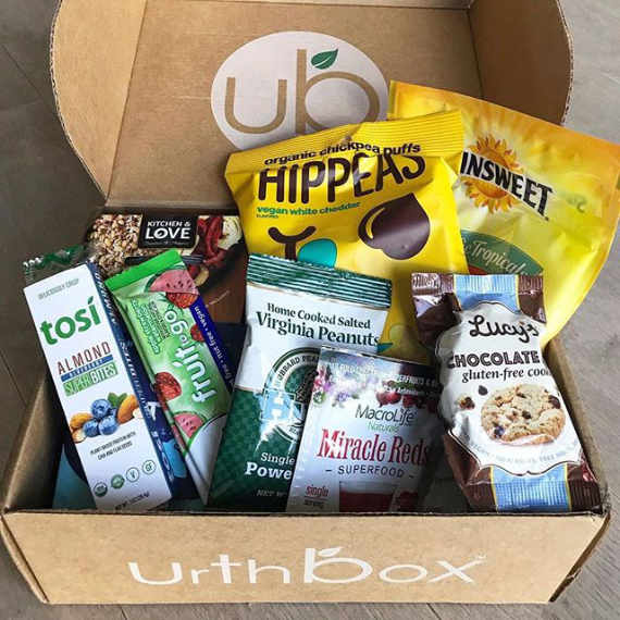"carton box saying ""urthboy"" with 10 different vegan snacks like chocolate cookies, almond bites, fruit bars and chickpea chips"
