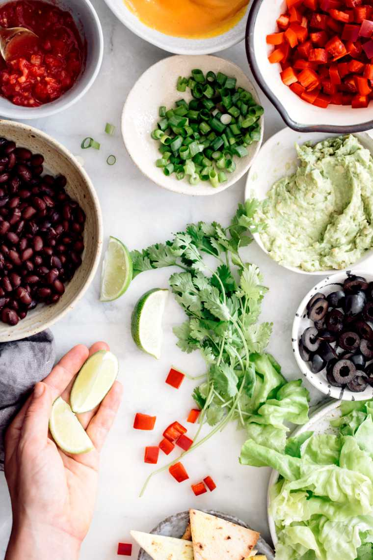 white table with bowls of vegan food like black beans, chopped bell pepper, olives, green onion, guacamole and salsa