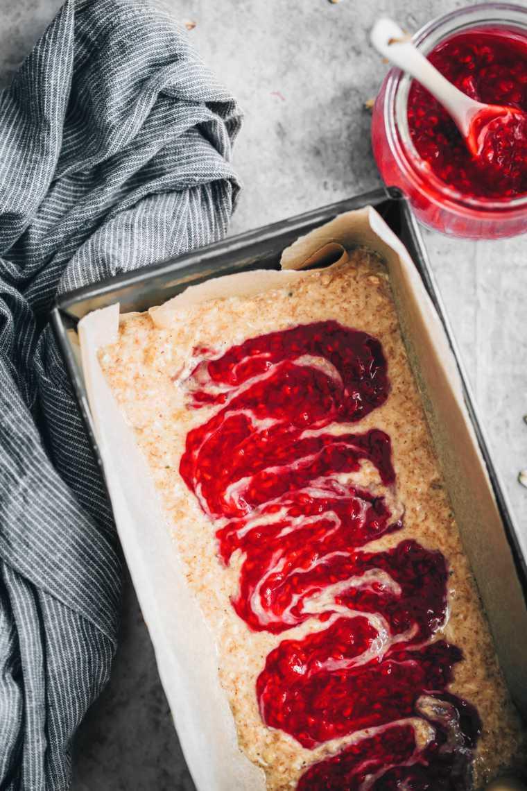 baking dish with vegan banana bread batter and raspberry jam