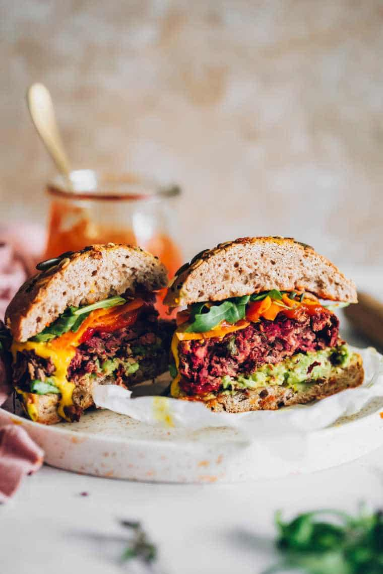 halved colorful plant-based burger with whole wheat buns on a white plate