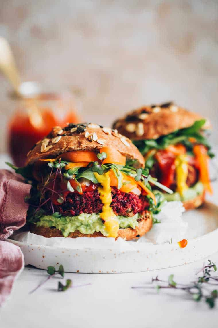 two large and colorfully stuffed beet burger patties in whole wheat buns with avocado, mustard, BBQ sauce, greens and carrot on a plate