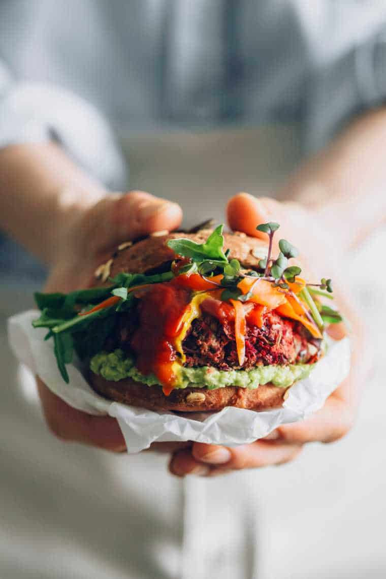 woman in blue shirt holding an assembled vegan burger with avocado, mustard and BBQ sauce in her hands
