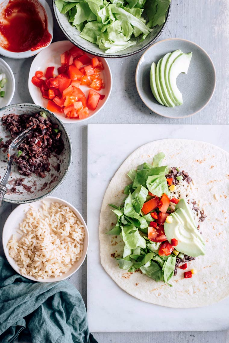 ingredients for vegan burrito, such as rice, bell peppers, avocado and beans, on a table