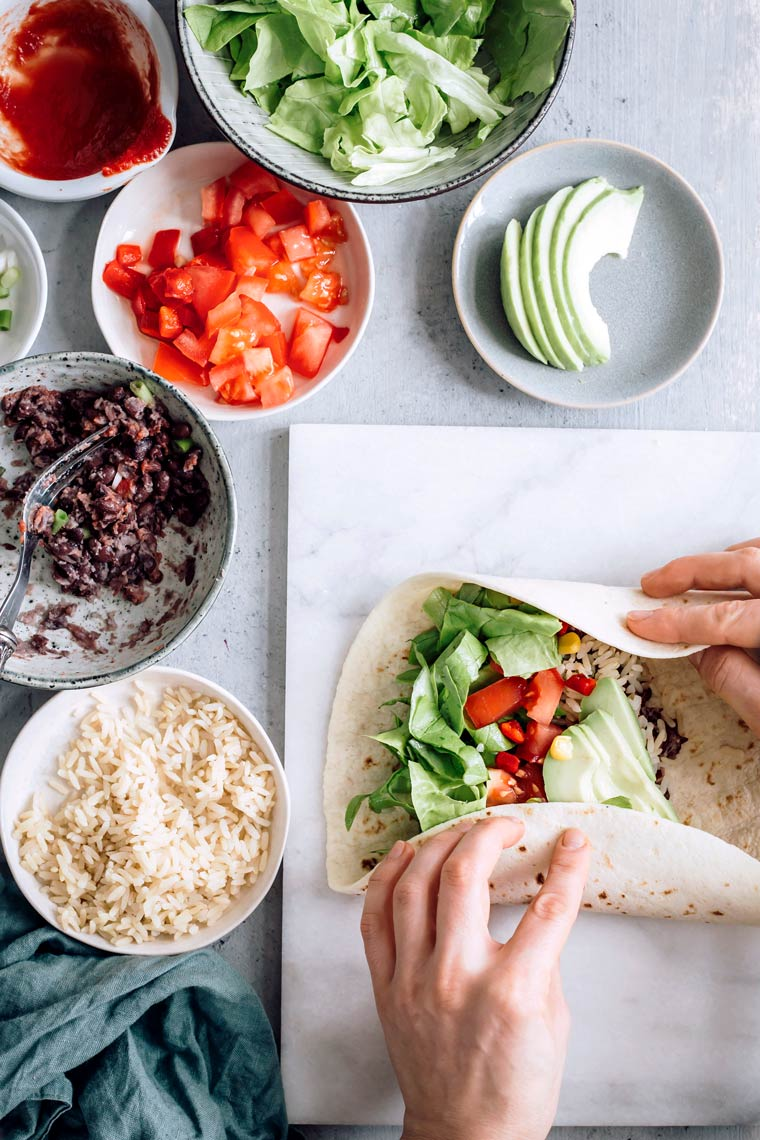 Woman rolling bean burrito on cutting board next to small bowls with vegetables