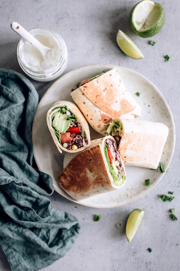 Finished vegan bean burrito cut into halves lying on plate