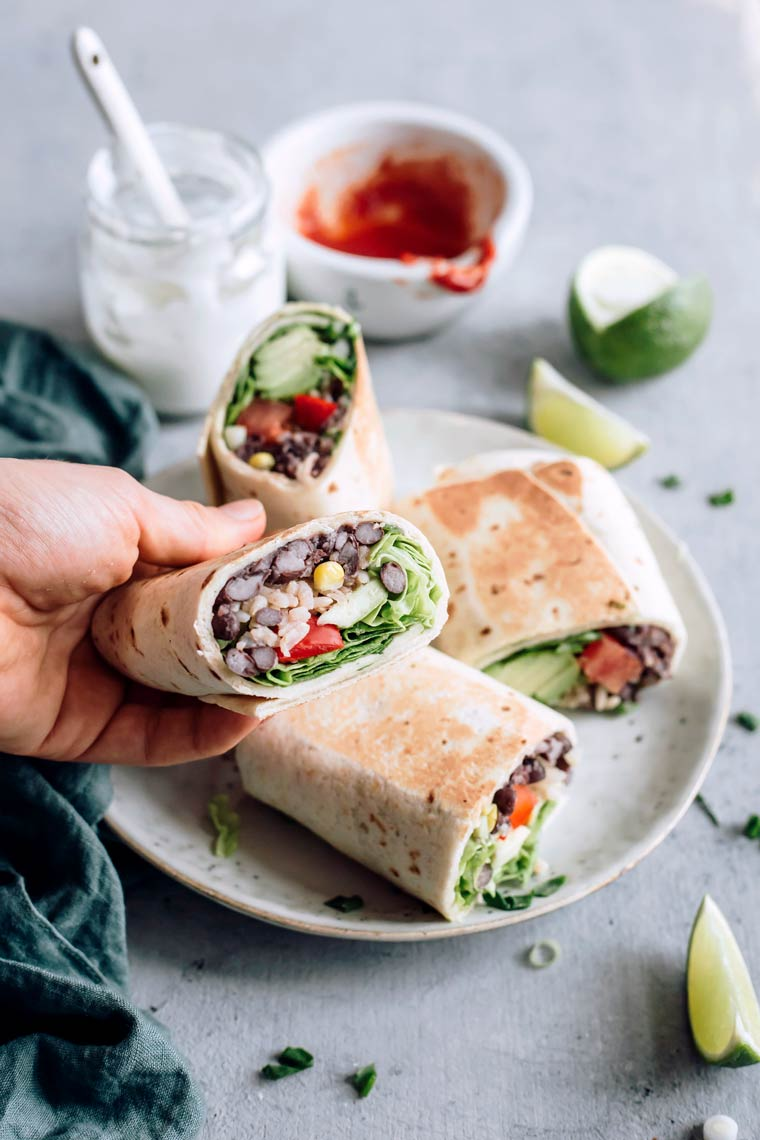Woman holding halved bean burrito in her hand over a plate of two more burritos