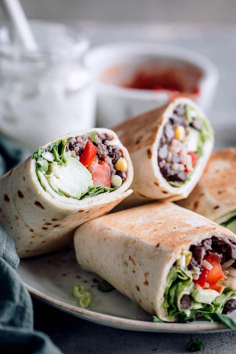 Close up of four bean burritos filled with vegetables on a plate with yogurt and tomato paste in the background
