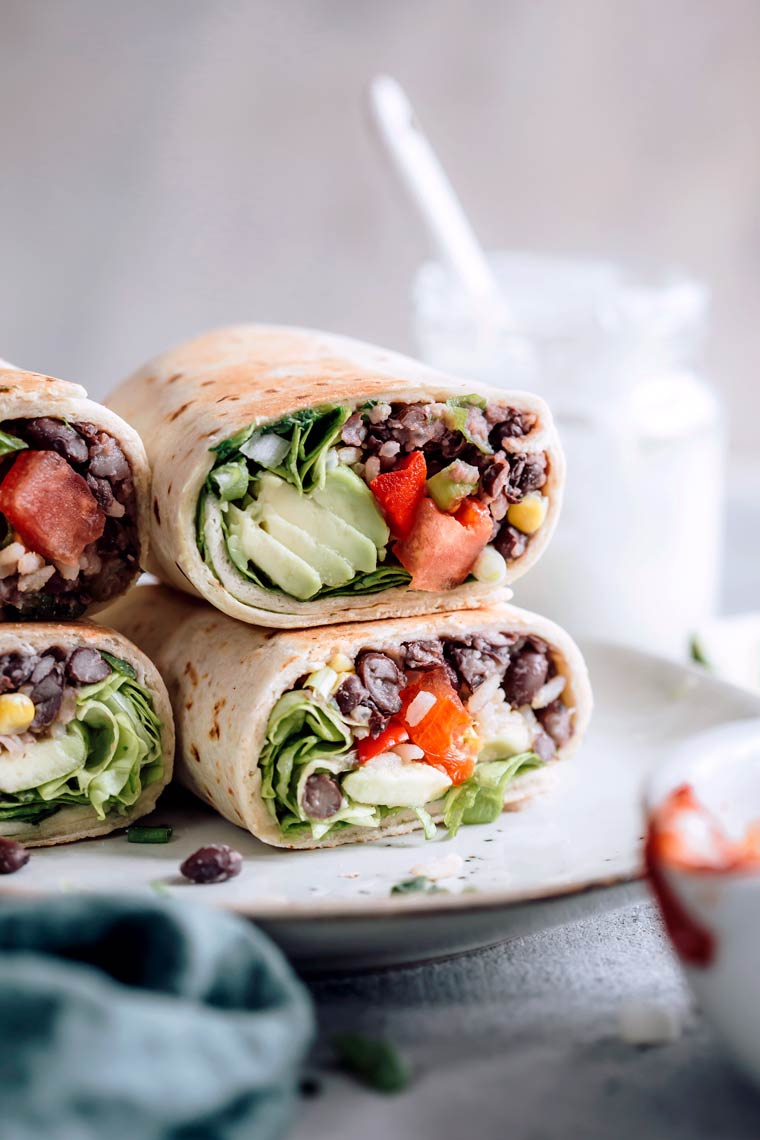 Close up of four colorful vegan burritos filled with avocado, rice and tomatoes