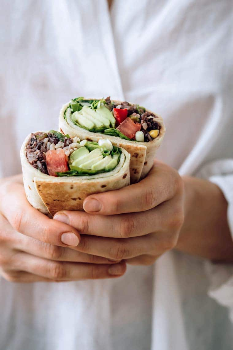 woman with white shirt holding two bean burritos filled with avocado and tomato