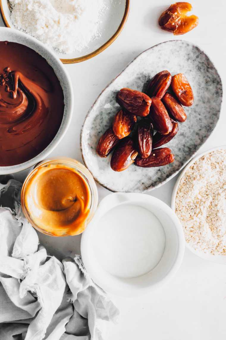 white table with different sized bowls containing ground oats, dates, almond flour, melted vegan chocolate and date caramel