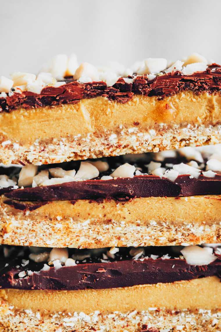 three no-bake vegan caramel slices topped with chopped almonds on top of each other