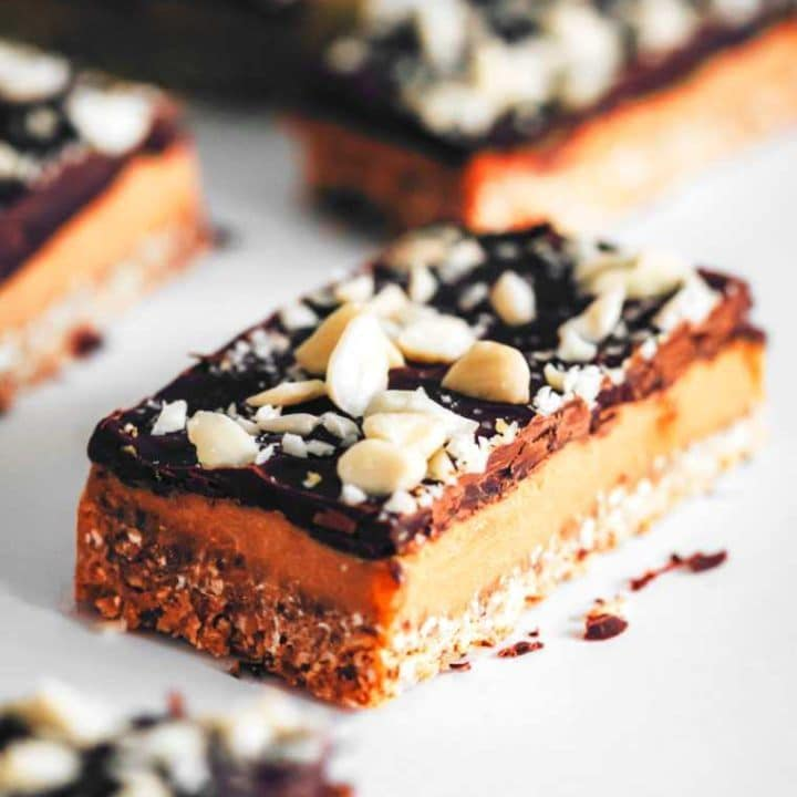 five no-bake vegan caramel slices with chocolate and almond topping on a white table