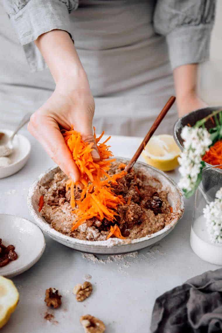 woman in apron standing next to a bowl with plant-based batter and putting shredded carrots on top of it