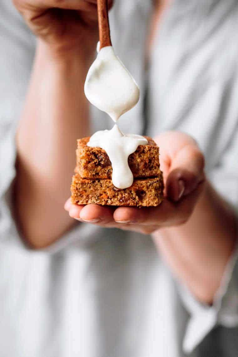 woman in white shirt holding two squares of oil free vegan carrot cake while putting some homemade cashew frosting on top of them