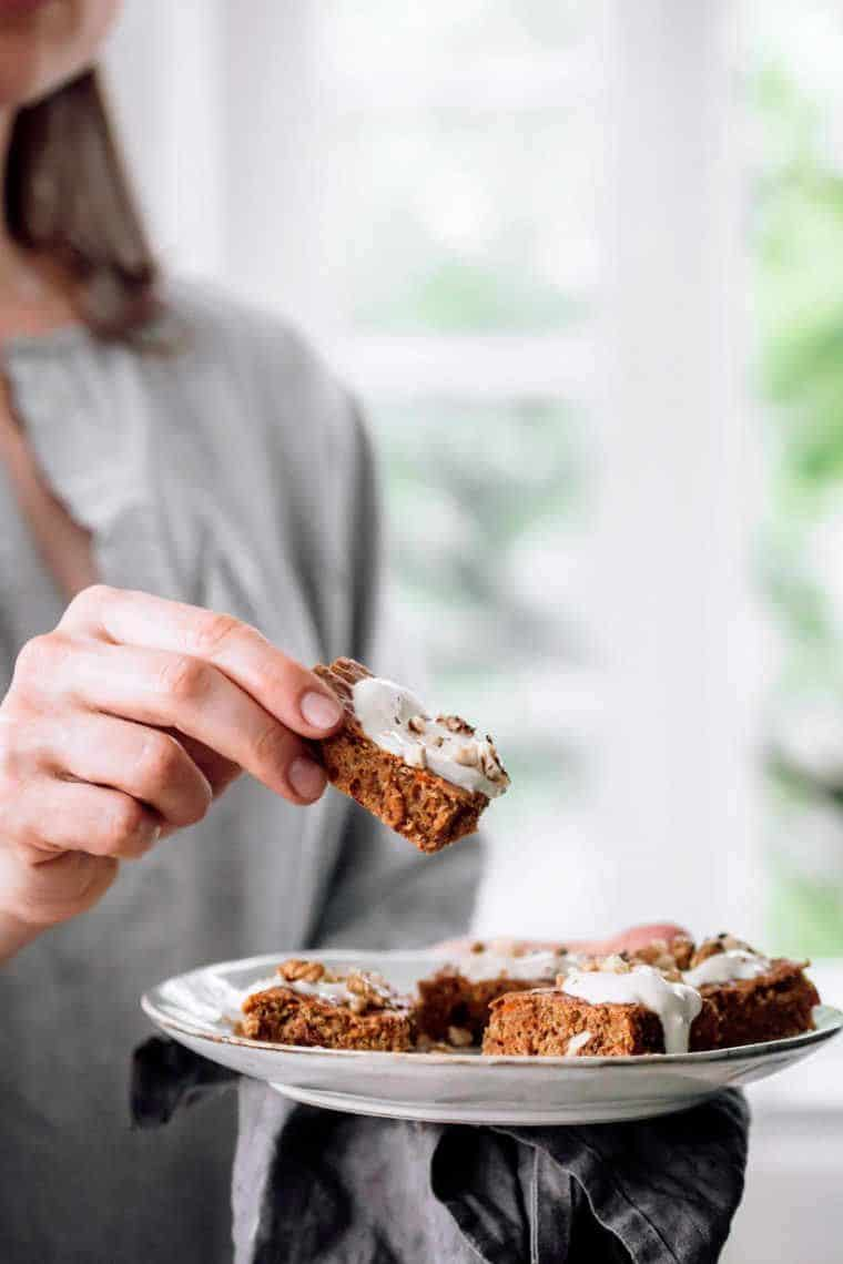 woman standing by a window with a place of plant-based carrot cake pieces and taking one to eat