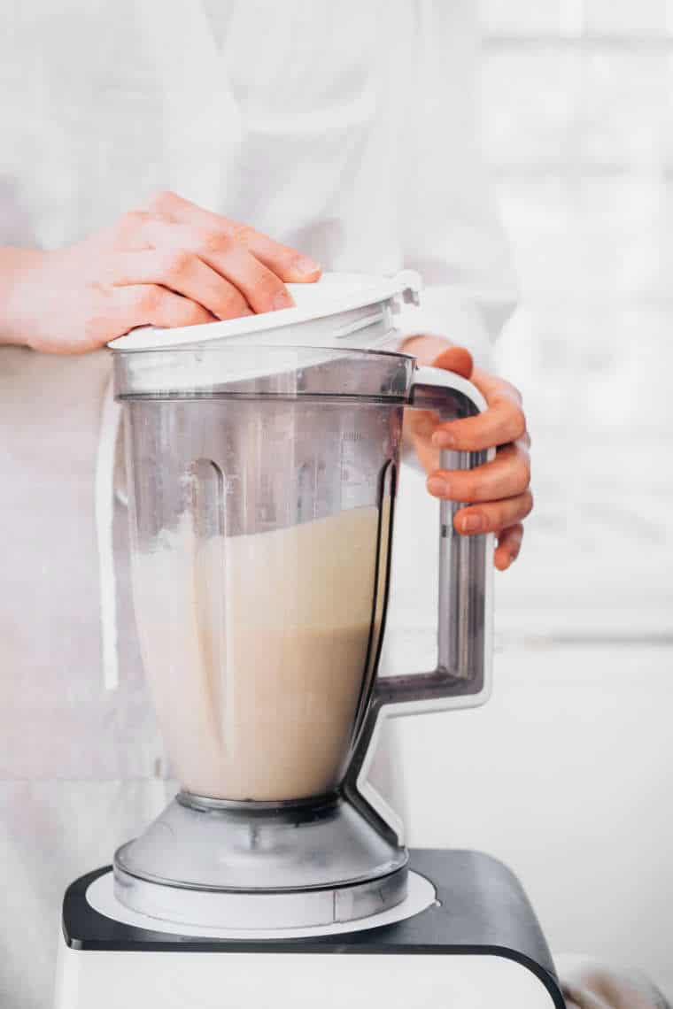 woman in white apron standing behind a blender jar with freshly made cashew mayo