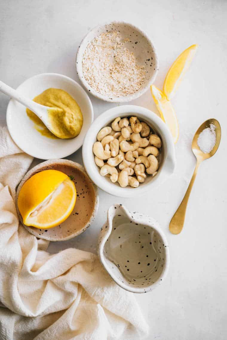 white table with different small bowls containing ingredients to make cashew mayonnaise: lemon juice, nutritional yeast, salt, mustard and cashews